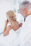 Arts die de ademhaling bij zijn patiënt luisteren stock afbeeldingen