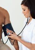 Arts die de bloeddruk van een klopje controleert Royalty-vrije Stock Fotografie