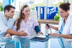 Arts die de bloeddruk van een zwangere patiënt met haar echtgenoot nemen Stock Fotografie