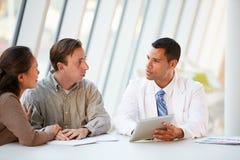 Arts die de Computer die van de Tablet met behulp van Behandeling bespreken met Patiënten Stock Afbeelding