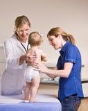 Arts die de controle van het babymeisje in artsenbureau geeft Stock Foto