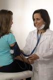 Arts die de druk-Verticaal van het Bloed van een Patiënt neemt Stock Afbeeldingen