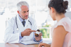 Arts die de fles van pillen verklaren aan patiënt Royalty-vrije Stock Fotografie