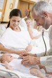 Arts die de hartslag van de baby met nieuwe moeder controleert Royalty-vrije Stock Foto's