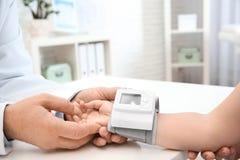 Arts die de impuls van het meisje met medisch apparaat in het ziekenhuis controleren, stock afbeeldingen