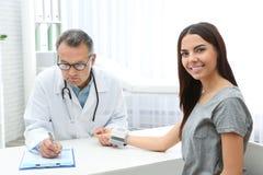 Arts die de impuls van de jonge vrouw met medisch apparaat controleren stock fotografie