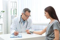 Arts die de impuls van de jonge vrouw met medisch apparaat controleren stock afbeeldingen