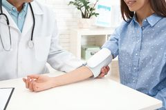 Arts die de impuls van de jonge vrouw met medisch apparaat in het ziekenhuis controleren royalty-vrije stock afbeeldingen