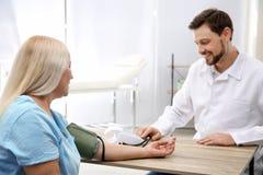 Arts die de impuls van de rijpe vrouw met medisch apparaat controleren stock foto
