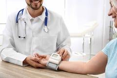 Arts die de impuls van de rijpe vrouw met medisch apparaat in het ziekenhuis controleren stock afbeelding