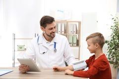 Arts die de impuls van weinig jongen met medisch apparaat controleren stock afbeelding