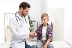 Arts die de impuls van weinig jongen met medisch apparaat controleren stock fotografie