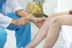 Arts die de kniereflex onderzoeken stock afbeeldingen