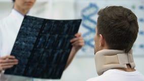 Arts die de mens in negatief x-ray onderzoeksresultaat van de schuim cervicaal kraag informeren stock videobeelden