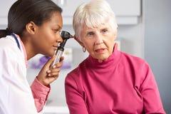 Arts die de Oren van de Hogere Vrouwelijke Patiënt onderzoeken stock foto