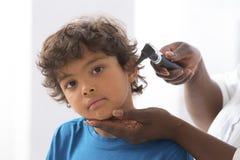 Arts die de oren van weinig jongen onderzoeken Stock Afbeeldingen
