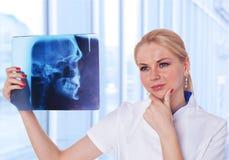 Arts die de resultaten van de Röntgenstraal van haar patiënt bekijkt Stock Afbeelding
