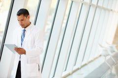 Arts die Digitale Tablet in Gang van het Moderne Ziekenhuis gebruiken Stock Foto's