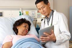 Arts die Digitale Tablet gebruiken die met Hogere Patiënt spreken Royalty-vrije Stock Foto