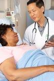 Arts die Digitale Tablet gebruiken die met Hogere Patiënt spreken Royalty-vrije Stock Afbeelding