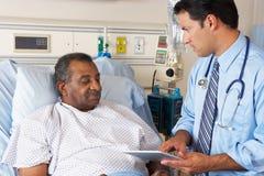 Arts die Digitale Tablet in overleg met Patiënt gebruiken Stock Afbeeldingen