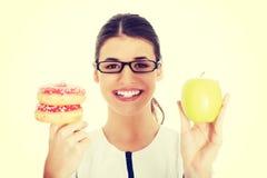 Arts die een appel houden en doughtnuts Royalty-vrije Stock Foto