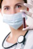 Arts die een bloedsteekproef bekijkt Stock Afbeeldingen