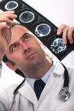 Arts die een CT aftasten analyseert Stock Afbeeldingen