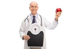 Arts die een gewichtsschaal en een appel houden Stock Afbeeldingen