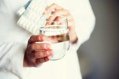 Arts die een glas water met drug, pillen, witte achtergrond houden De ruimte van het exemplaar Het concept van de geneeskunde stock foto