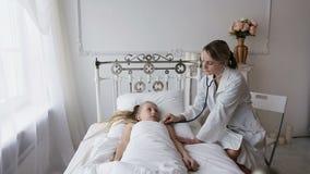 Arts die een kind met een stethoscoop auscultating stock footage