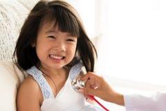 Arts die een klein meisje onderzoeken door stethoscoop te gebruiken royalty-vrije stock fotografie
