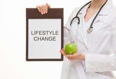 Arts die een klembord en een groene appel houden Stock Afbeeldingen