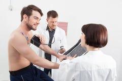 Arts die een mannelijke patiëntenbloeddruk nemen Stock Afbeelding