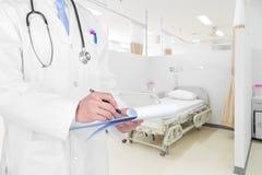 Arts die een medisch voorschrift met medische achtergrond schrijven stock foto's