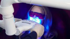 Arts die een mooie jonge blonde vrouw voor laser voorbereiden die tandenprocedure witten stock videobeelden