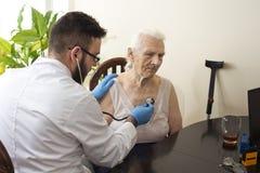 Arts die een oude vrouw met een stethoscoop in een artsen` s bureau onderzoeken stock foto