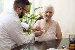 Arts die een oude vrouw met een stethoscoop in een artsen` s bureau onderzoeken stock afbeelding