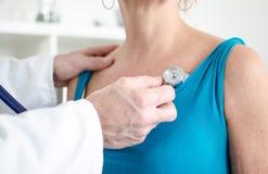 Arts die een patiënt met een stethoscoop onderzoeken Royalty-vrije Stock Afbeeldingen