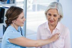 Arts die een patiënt met stethoscoop onderzoeken Stock Fotografie