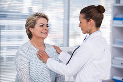 Arts die een patiënt met stethoscoop onderzoeken Stock Foto
