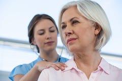 Arts die een patiënt met stethoscoop onderzoeken Stock Foto's
