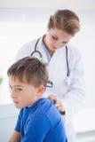 Arts die een patiëntenhals onderzoeken Stock Fotografie