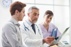 Arts die een patient& x27 onderzoeken; s röntgenstraal Stock Foto's