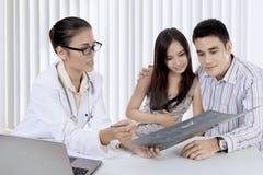 Arts die een Röntgenstraalresultaat verklaren aan haar patiënt stock fotografie