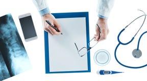 Arts die een voorschrift op een klembord schrijven Stock Afbeeldingen