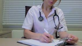 Arts die een voorschrift schrijven bij bureau stock footage