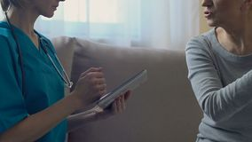 Arts die elektronisch medisch dossier in tablet houden, die oude vrouw thuis onderzoeken stock video