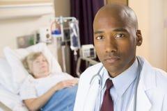 Arts die Ernstig in de Zaal van het Ziekenhuis kijkt Stock Afbeelding