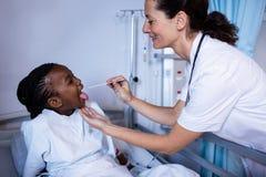 Arts die geduldige koorts van thermometer controleren tijdens bezoek in afdeling Stock Foto's